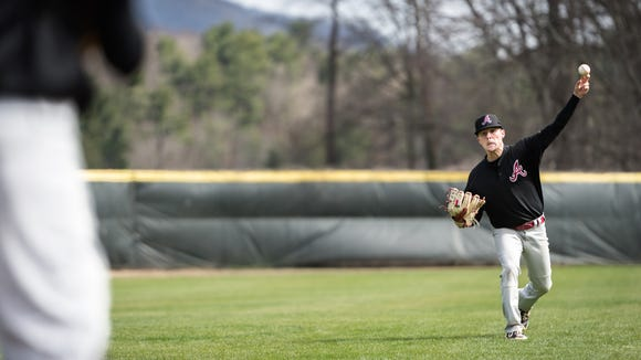 Asheville high school junior, Graham Hooker, pitcher and outfielder for the baseball team, warms up during practice Monday, March 26, 2018.