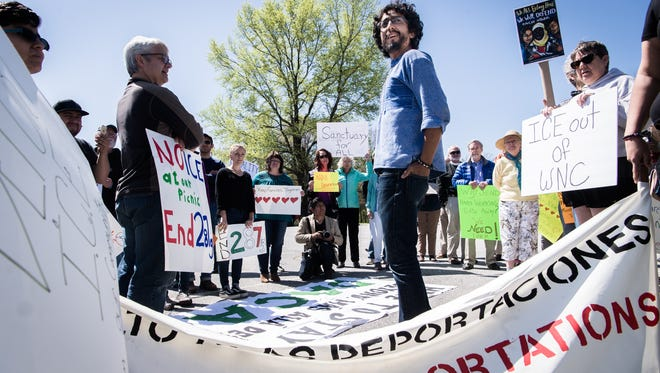 Bruno Hinojosa, of the local advocacy organization, CIMA, or  Compañeros Inmigrantes de las Montañas en Acción, which translates to Migrant Fellows of the Mountains in Action, helps organize demonstrators at Jackson Park in Hendersonville where ICE, Homeland Security and other local law enforcement agents gathered for a picnic Friday, April 20, 2018.