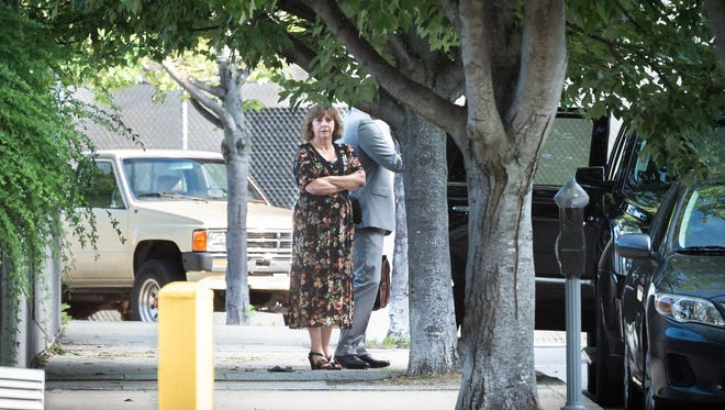 Wanda Greene, former Buncombe County Manager, waits by an SUV with her attorneys, Noell Tin and Thomas Amburgey before walking to the federal courthouse Wednesday, June 13, 2018, to appear before a U.S magistrate judge where she will be indicted on additional charges of using public money to buy life insurance policies for herself and other employees. Greene was indicted in April on charges of wire fraud, conspiracy, embezzlement and aiding and abetting.