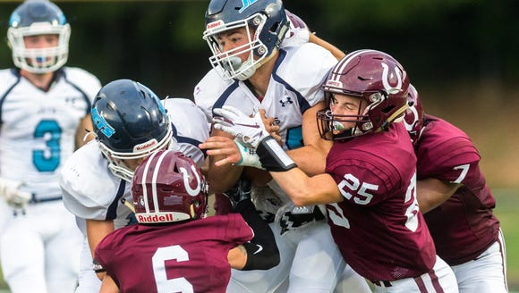 Enka's Jackson Smith is tackled by several Owen players