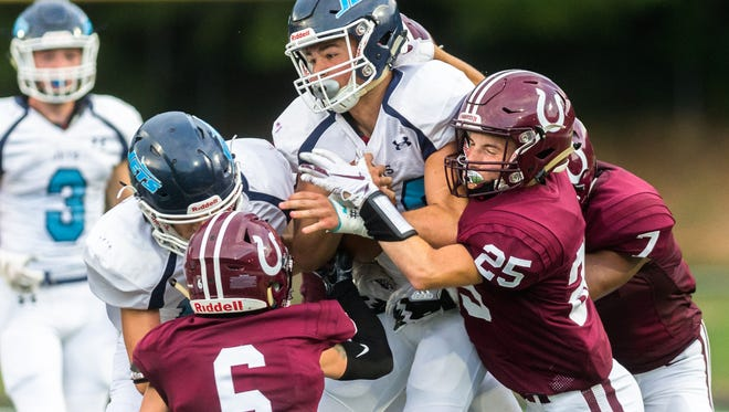 Enka's Jackson Smith is tackled by several Owen players during their opening game Friday, August 17, 2018, losing 34-7.