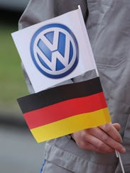 Workers hold German and Volkswagen logo flags before
