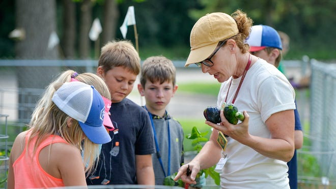 Stearns County Master Gardener Jean Januschka Ebnet, right, talks with participants in the children's Garden Camp as they tend and harvest the garden Tuesday, July 19, 2016, at the Stearns History Museum.