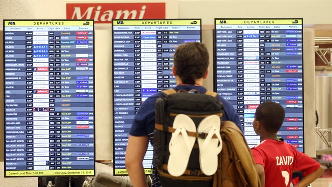 Passengers check the departure board at Miami International Airport on Thursday, Sept. 7, 2017.