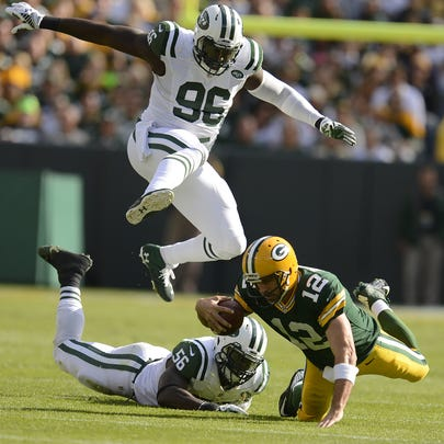Green Bay Packers quarterback Aaron Rodgers (12) falls down while being chased New York Jets' Muhammed Wilkerson (96) and Demario Davis (56) in the first quarter during Sunday's game at Lambeau Field.