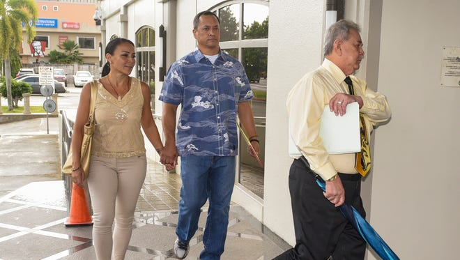 In March 29 file photo, attorney Mark Smith, center, walks hand-in-hand with ex-wife Clare Calvo as they are led into the District Court of Guam building by his attorney, David Lujan.