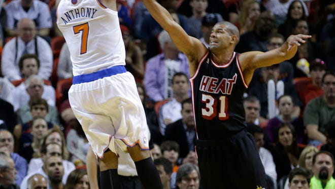 The Knicks' Carmelo Anthony, left, shoots over Miami's Shane Battier during the first half on Thursday night. Anthony scored 29 points, but the Knicks lost 108-82.