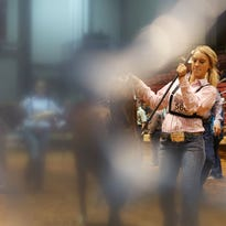 Seen through a hole in the plastic bunting, Madi Barrow, 14, of Winnie, Texas, leads a heifer around the arena during the Junior Beefmasters Breeders Association's national show at the Ike Hamilton Expo Center in West Monroe on Friday.