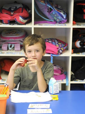 Silver Stage Elementary School first-grader Tristan Chernault eats an apple in class.