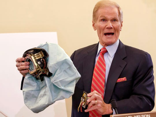 Senate Commerce Committee member Sen. Bill Nelson, D-Fla. holds an example of the defective airbag made by Takata of Japan that has been linked to multiple deaths and injuries in cars driven in the U.S. during the committee's hearing Nov. 20, 2014, on Capitol Hill in Washington.