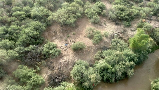 """The stranded group created an """"SOS"""" message out of debris found in the river, officials said."""