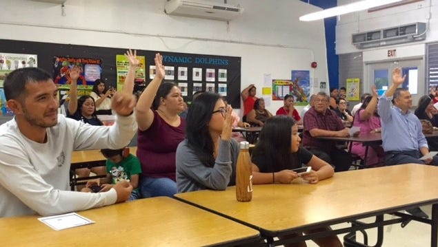 Parents of students in public schools, including Sen. Dennis Rodriguez, far right, raise their hands during the Guam Education Board's Wednesday night work session at Merizo Martyrs Elementary School, to seek public input on cost-cutting and revenue-enhancement measures to help address a $19.6 million education budget shortfall for fiscal 2018, as a result of the federal tax reform law.