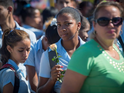 Schoolchildren wait in line to view Cuban icon Fidel