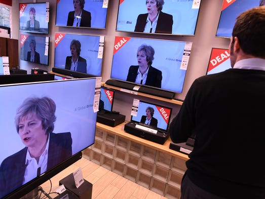 An employee changes the channels of televisions, on