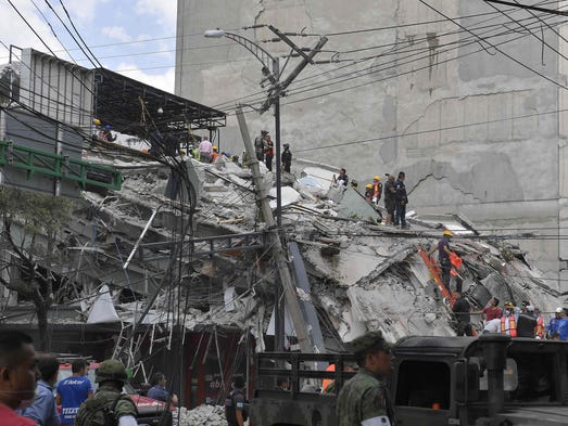 Rescuers work on the rubble from a building knocked
