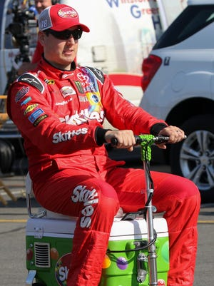 Kyle Busch rides a motorized scooter at Charlotte Motor Speedway.