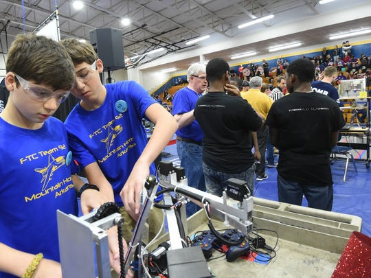Timothy Carroccio (left) and Trent Guthrie (right), Members of the Junior Bomb Squad, work on their robot Saturday before a match. The team was a finalist.
