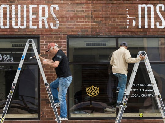 Painters Ches Perry (left) and Jonathan Jardin of Chicago-based Rightway Signs work at Flowers for Dreams, 134 W. Pittsburgh Ave.