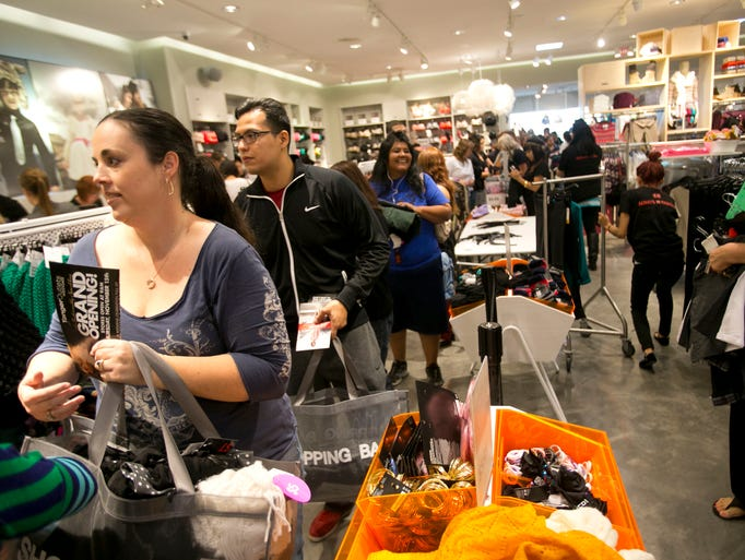 Customers wait in line to check out at the H&M store during the grand opening of the Tanger Outlets Westgate in Glendale on Thursday, November 15, 2012.