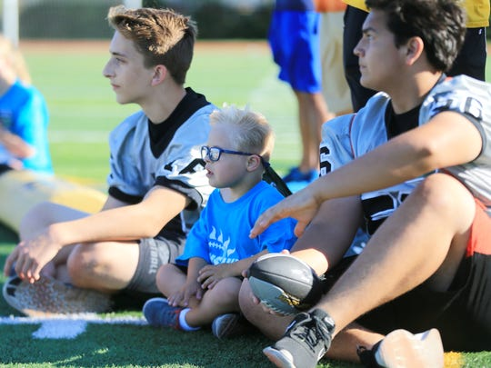 This Sunshine's camper (center) and a couple Plymouth football players take a break on the sidelines.
