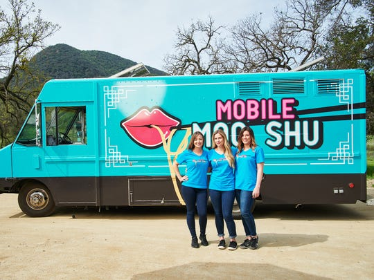 """The Mobile Moo Shu food truck team (Marley Vanderbrook, Chelsea Smith, Michelle Gautier) in front of their truck, as seen on """"The Great Food Truck Race,"""" Season 9."""