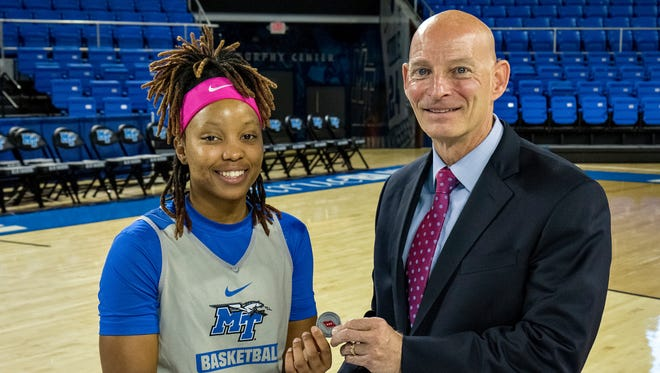 MTSU point guard Ty Petty, left, stands with retired Lt. Gen. Keith Huber at the Murphy Center on Friday. Petty was presented with a coin after Huber noticed her leadership during practice this week.