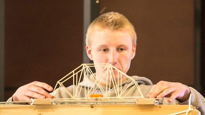 Susquehannock junior Jason Weger, centers one of the competition bridges on the bridge breaker, during the 23rd annual High School Bridge Building Competition at Penn State York Saturday, March 4, 2017, in Spring Garden Township. Amanda J. Cain photo