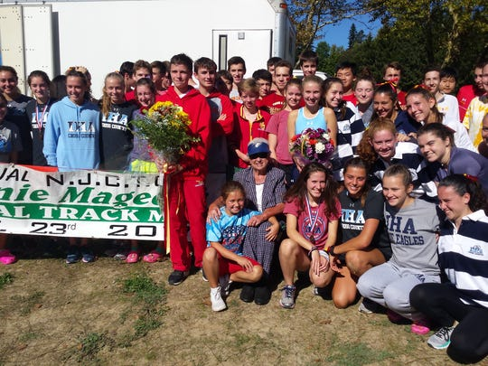 Bergen Catholic and IHA cross-country teams presenting flowers to Mrs. Evelyn Magee, 89, wife of the late Bernie Magee for whom a meet is named and mother of the late Bill Magee, former BC track and cross-country coaches. Flower presenters are freshman James Adams of BC and junior Emily Primavera of IHA on Saturday, Sept. 23, 2017.