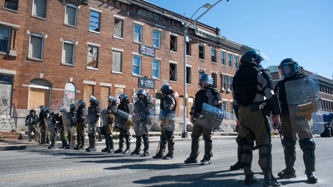 epa04724458 Maryland State Troopers stand in riot gear at the intersection of North Avenue and Pennsylvania Avenue in the wake of protests for the death of Freddie Gray in Baltimore, Maryland, USA, 28 April 2015. Gray died of spinal cord injuries on 19 April while in police custody; the US Justice Department announced that they are launching their own investigation into the case.  EPA/NOAH SCIALOM ORG XMIT: NS21