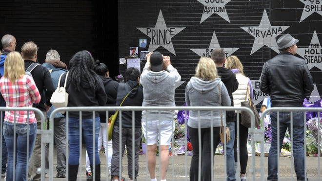 Fans gather Friday, April 22, 2016, at the star bearing Prince's name on an outside wall of First Avenue, the nightclub where Prince got his start, in Minneapolis, Minnesota.