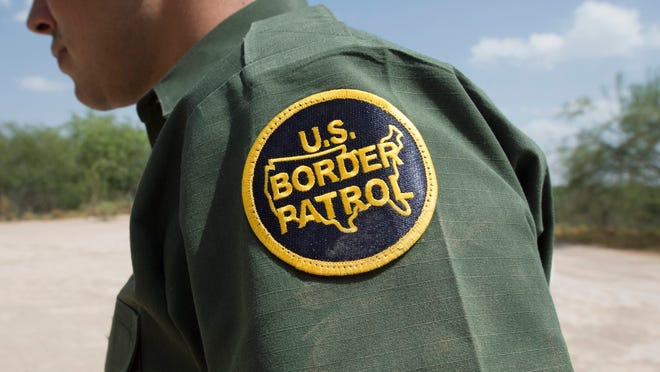 Border Patrol agent walks on the river road by the US-Mexican border at the Rio Grande River.