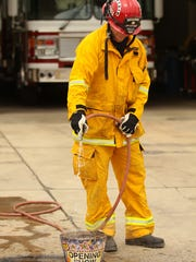 Capt. Bryant Phillips uses a garden hose while demonstrating how to fully extinguish and discard fireworks on Thursday, June 26, 2014 during a firework safety presentation by Cathedral City Fire Department.