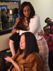 Erika Hernandez holds 26 inches of her hair that was cut to create a wig for Kim Ross, in the background embracing stylist Angelline Smalls on Saturday in the City of Poughkeepsie. Ross was recently diagnosed with breast cancer, and Hernandez generously offered to donate her hair to create a wig for Ross.