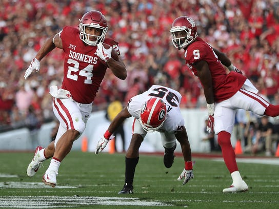 Oklahoma running back Rodney Anderson breaks away from Georgia defensive back Aaron Davis for a touchdown during the second quarter in the College Football Playoff Semifinal at the Rose Bowl NCAA college football game on Monday, Jan. 1, 2018, in Pasadena. (Curtis Compton/Atlanta Journal-Constitution via AP)