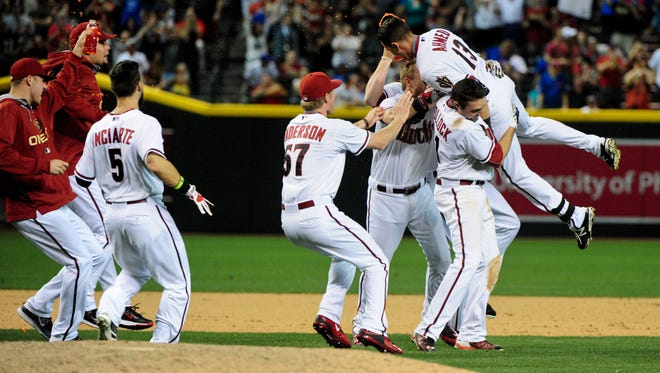Arizona Diamondbacks shortstop Nick Ahmed celebrates with teammates after hitting a walk-off single in the thirteenth inning to defend the Chicago Cubs 5-4 at Chase Field.