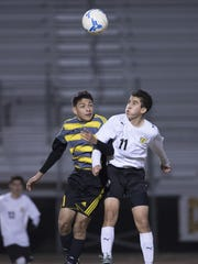 Edison's Jesus Sandoval, left, and Golden West's John Hernandez go up for a kicked ball in a Central Section Division II high school boys soccer championship on Tuesday, February 28, 2017. Hernandez' goal lifted Golden West to the 3-2 win in overtime.