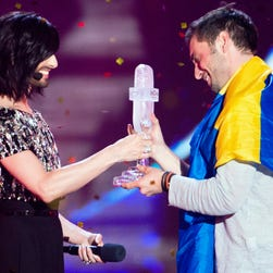 Austrian singer Conchita Wurst (L) hands over the ESC trophy to Mans Zelmerlow representing Sweden for his victory during the Grand Final of the 60th annual Eurovision Song Contest (ESC) at the Wiener Stadthalle in Vienna, Austria, 23 May 2015. There are 27 finalists from as many countries competing in the grand final.