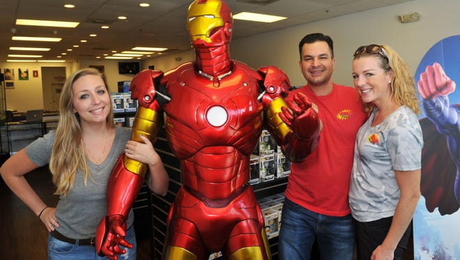 Left to right, store manager Melissa Walsh, a life size Iron Man, store owner Peter Pappas, and his wife, Kerry. Viera Comics has opened at the Park Place at Suntree at 7640 North Wickham Road, next to Tuscany Grill. Their grand opening will be Oct.10.