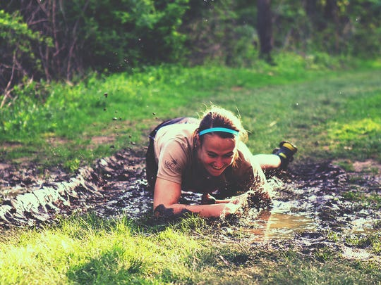 Young Life volunteer Lauren Yurjevic practiced crawling in the mud in preparation for a past Beast of the East Fork charity run. This year's event is June 2 at East Fork State Park in Clermont County