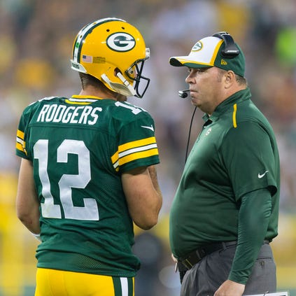 Aug 22, 2014; Green Bay, WI, USA; Green Bay Packers quarterback Aaron Rodgers (12) talks with head coach Mike McCarthy during the first quarter against the Oakland Raiders at Lambeau Field. Mandatory Credit: Jeff Hanisch-USA TODAY Sports