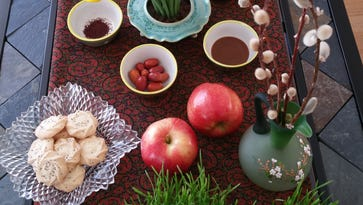 """A Nowruz table is set with seven items – traditionally, apples, grass, dried sumac berries, dried fruit of the oleaster tree, coins, garlic and a semolina pudding – signifying renewal, love, kindness, service and rebirth. All seven of the symbols begin with an """"s"""" sound, and the table is called a """"Haft-sin"""" – for seven """"S"""". This is the haft-sin table Marzie Jafari set for her Nowruz celebration in New City this year."""