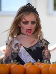 Sophie Saunders (left), 7, dressed as a zombie prom queen, and Elyssa Morrow, 7, dressed as a witch, decorated pumpkins at last year's Hobgoblins on Main Street.