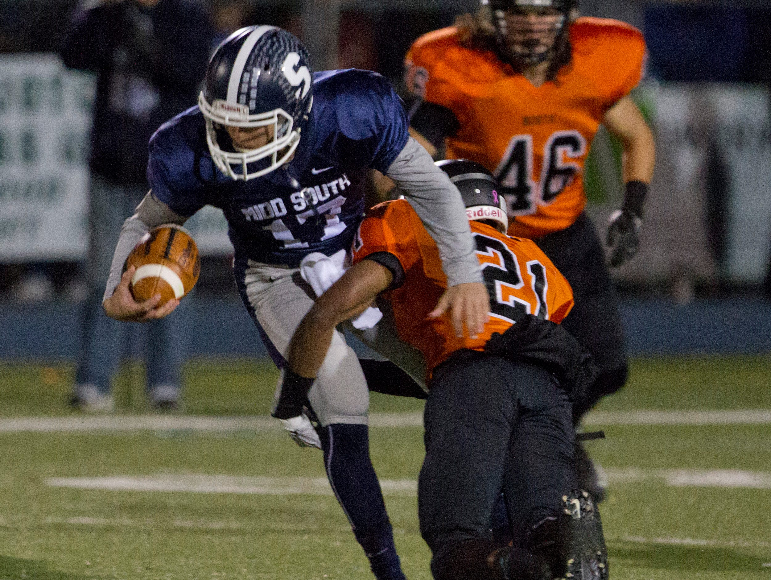 Middletown South's Matt Mosquera gains some yardage before being brought down by Middletown North's Dwight Wilkerson during first half action. Middletown North vs Middletown South in NJSIAA North II Group IV semifinal football in Middletown, NJ on November 20, 2015