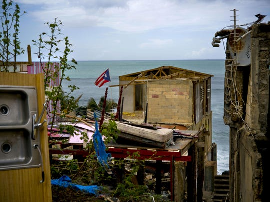 In this Oct. 5, 2017 file photo, a Puerto Rican national flag is mounted on debris of a damaged home in the aftermath of Hurricane Maria in the seaside slum La Perla, San Juan, Puerto Rico. An independent investigation ordered by Puerto Rico's government estimates that nearly 3,000 people died as a result of Hurricane Maria.