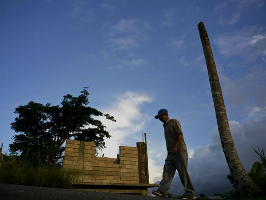 In this Sept. 8, 2018, file photo, Ramon Alicea Burgos walks past his palm tree, with its top broken off one year ago by Hurricane Maria one outside his partially rebuilt home in the mountain town of Barranquitas, Puerto Rico. A fight between President Donald Trump and Democrats over hurricane relief for Puerto Rico is imperiling a widely backed disaster aid bill that is a top priority for some of Trump's southern GOP allies.