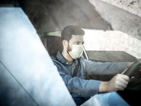 A ride hailing driver wearing a mask inside the vehicle.