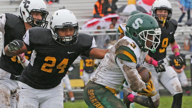 Martin Luther running back Darios Crawley-Reid (right) scampers through the mud last year. Crawley-Reid has twice set the school single-game rushing record this season, leading the Spartans to Level 2.