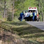 A man injured after a helicopter crashed while working a controlled burn is transported from an ambulance on Martha Redmund Road in Harrison County to a LifeFlight medevac helicopter nearby in an clearing on Monday. The other two people aboard the helicopter were killed.