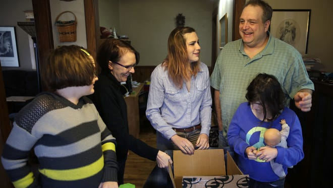 Emma Broeniman (left), her mother, Amie, sisters Allie (center) and Delaney, and father, Jim, share a laugh in their kitchen after going through a care package of Green Bay Packers memorabilia that arrived  earlier this month at their Appleton home.