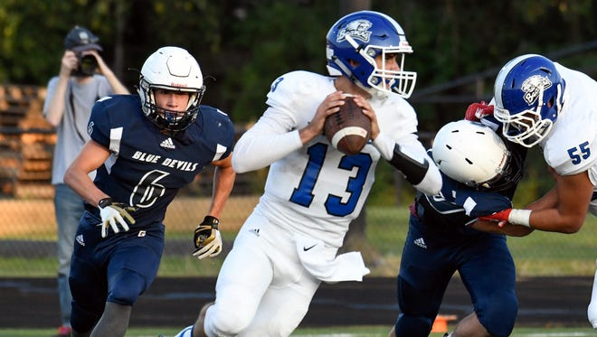 Harper Creek QB Jackson Malone (13) drops back to pass during game action earlier this season.